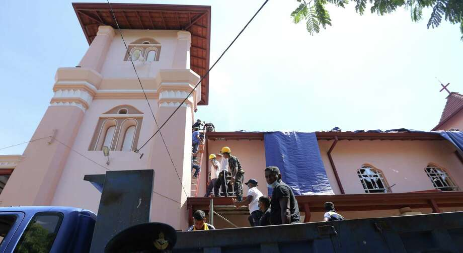 Workers inspect bomb damage outside St. Sebastian's Church in Negombo, Sri Lanka, on April 22, 2019. Photo: Bloomberg Photo By Tharaka Basnayaka / Bloomberg