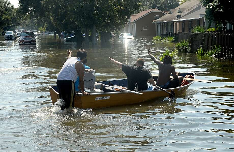 Port Arthur residents wave to neighbors as they make their way by boat through their flooded roadways Thursday.  Photo taken Thursday, August 31, 2017 Kim Brent/The Enterprise Photo: Kim Brent / Beaumont Enterprise / BEN
