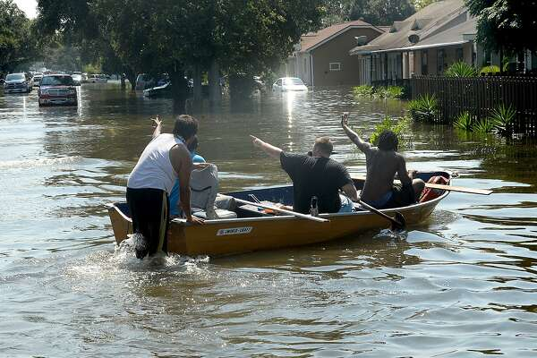 Port Arthur residents wave to neighbors as they make their way by boat through their flooded roadways Thursday. Photo taken Thursday, August 31, 2017 Kim Brent/The Enterprise