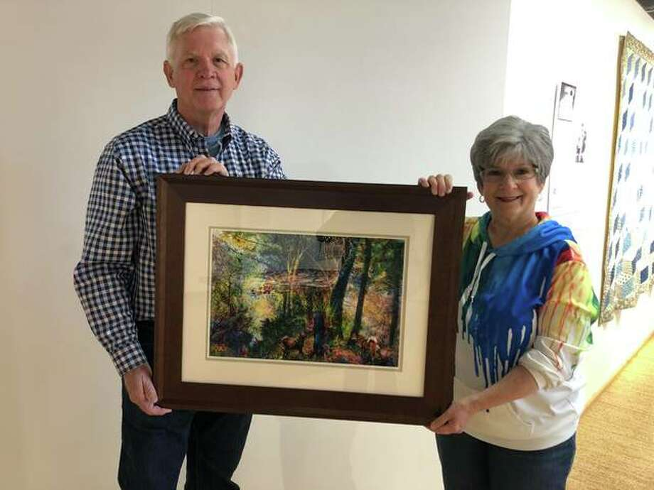 "John Dillaplain, GEAG's exhibit chairperson, right, and Marty Spears, longtime GEAG member, hold a piece of artwork that will be in the GEAG's exhibit starting Friday. The piece, ""Mushroom Hunters"" is one of three pieces in the show made by artist Ron Vivod. Photo: Julia Biggs 