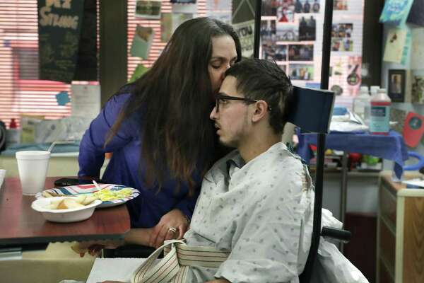 Kamini Del Barba leans over and kisses her son as he prepares to leave for physical therapy.