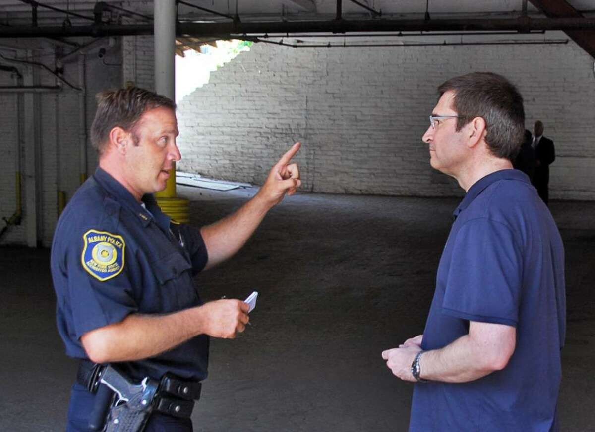 Officer Glenn Szelest, left, on Tuesday explains to parking lot tenant Todd Sisley of Albany, that he can't get to his car because of a collapsed wall at a private parking garage at 180 Lancaster St. in Albany. (John Carl D'Annibale / Times Union)