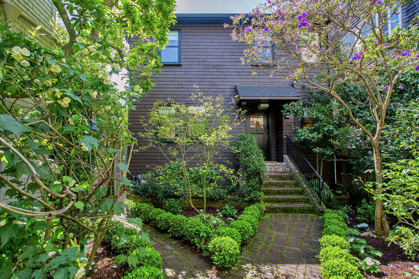 The wood-shingled home sits behind a lush garden.