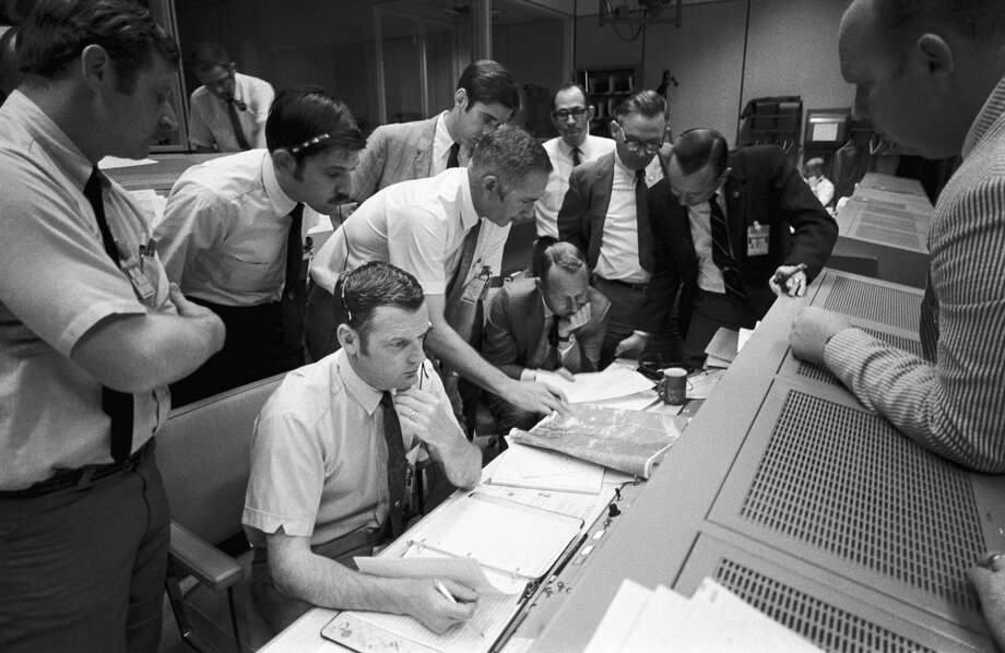 A group of flight controllers gathers around the console of Glynn S. Lunney (seated, nearest camera), the flight director, in Mission Control Center on April 15, 1970 at what was then called the Manned Spacecraft Center. Among those looking on is Dr. Christopher C. Kraft, deputy director of the space center, standing in a black suit, on right. When this photograph was taken, the Apollo 13 lunar landing mission had been canceled and the problem-plagued Apollo 13 crew members were attempting to bring their crippled spacecraft back home. Photo: NASA