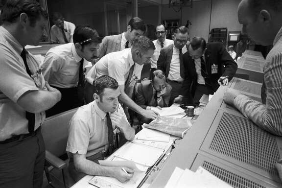 A group of flight controllers gathers around the console of Glynn S. Lunney (seated, nearest camera), the flight director, in Mission Control Center on April 15, 1970 at what was then called the Manned Spacecraft Center. Among those looking on is Dr. Christopher C. Kraft, deputy director of the space center, standing in a black suit, on right. When this photograph was taken, the Apollo 13 lunar landing mission had been canceled and the problem-plagued Apollo 13 crew members were attempting to bring their crippled spacecraft back home.