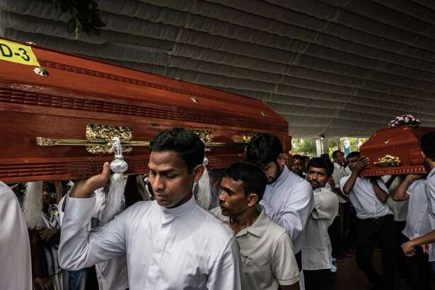 Two caskets are carried following a funeral service for victims of the Easter Sunday bombings on April 23, 2019, at St.Sebastian's church in Negombo, Sri Lanka.