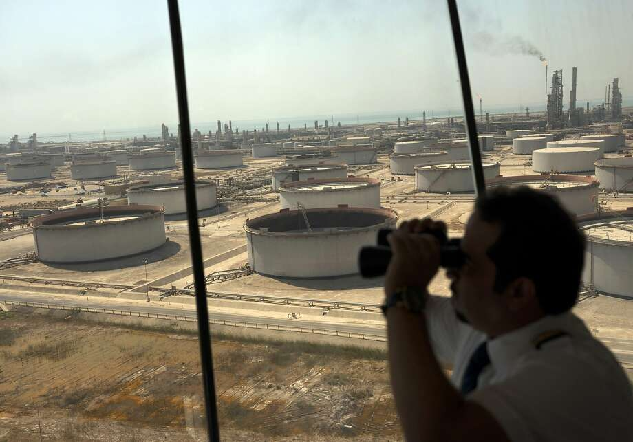 An employee uses binoculars to look toward the Arabian Sea in the Port Control Center at Saudi Aramco's Ras Tanura oil refinery and terminal in Ras Tanura, Saudi Arabia, on Oct. 1, 2018.  Photo: Simon Dawson, Bloomberg