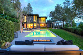 A lap pool stretches beside 11 Rock Road in Kentfield, and the landscaped backyard includes a lawn and gas fire pit.