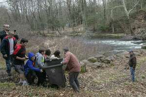Spencer Meyer, of Guilford, bottom center, helps children carry a bin containing a large trout to the Quinnipiac River during the annual fish stocking along the Quinnipiac River Gorge Trail in Meriden, Conn., Mon., April 8, 2019. (Dave Zajac/Record-Journal via AP)