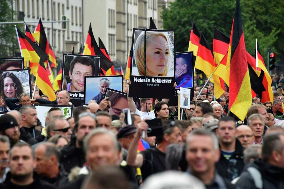 (FILES) In this file photo taken on September 01, 2018 demonstrators hold up placards showing portraits of victims of refugees during a protest organised by the far-right Alternative for Germany (AfD) party, in Chemnitz, eastern Germany. - Alternative for Germany (AfD) hopes the strategy that made it the biggest opposition party in 2017's general election will pay off once again next month, when voters elect a new European Parliament. (Photo by John MACDOUGALL / AFP)JOHN MACDOUGALL/AFP/Getty Images Photo: JOHN MACDOUGALL / AFP/Getty Images / AFP or licensors