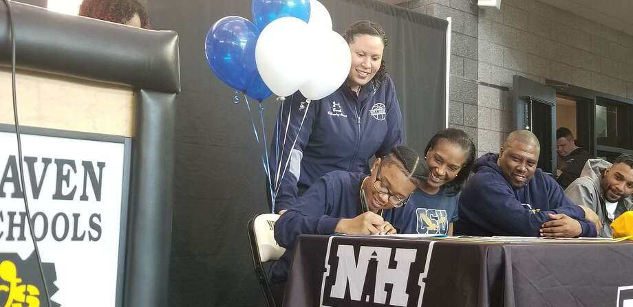 Hillhouse's Tyree Allen, far left, signs a national letter of intent to play basketball at Coppin State. Looking on are Hillhouse coach Catrina Hawley-Stewart (behind), mom Stacey Allen, stepfather Maurice Williamson and older brother Tavon. Photo: Joe Morelli / Hearst Connecticut Media