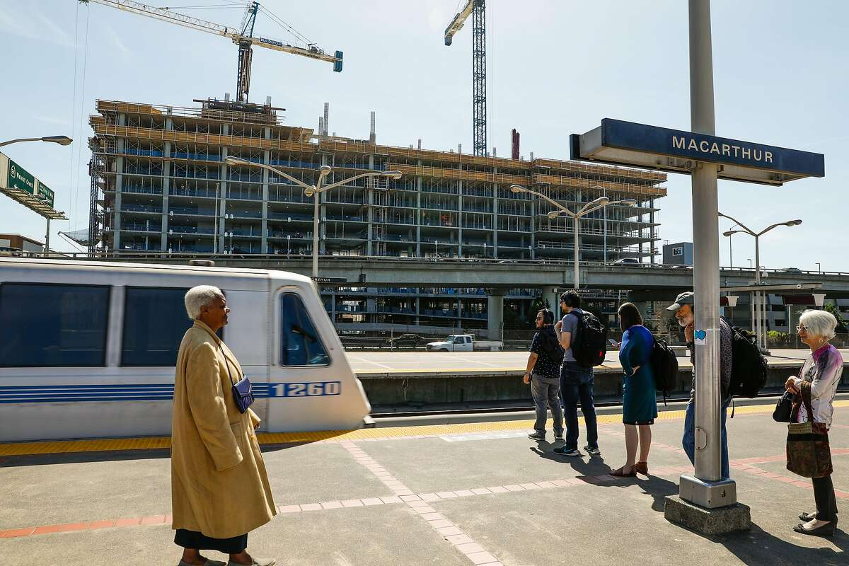 People wait to board the BART at the MacArthur BART station while an apartment building is seen under construction in Oakland.