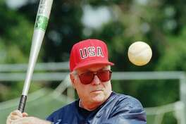 USA Olympic women's softball coach Ralph Raymond hits to the team during practice at the South Commons softball complex in Columbus, Ga., on June 4, 1996. Raymond, who led the Brakettes to 17 ASA national titles, passed away on Tuesday.