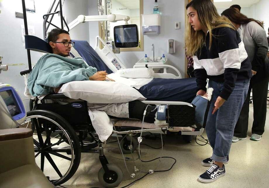 Drisa Del Barba, Dez's sister, helps him adjust his remaining leg. Photo: Bob Owen, San Antonio Express-News / ©2019 San Antonio Express-News