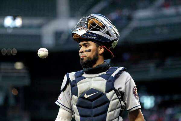Houston Astros catcher Robinson Chirinos pops a ball up as he walks off the field against the Seattle Mariners in a baseball game Saturday, April 13, 2019, in Seattle. (AP Photo/Elaine Thompson)