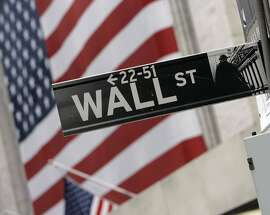 The flags on the facade of the New York Stock Exchange are a backdrop for a Wall Street street sign, Thursday morning, Aug. 16, 2007. U.S. stocks appeared headed for another sharp retrenchment Thursday after a move by Countrywide Financial Corp. confirmed fears of widening problems with some mortgages and tighter access to credit.  (AP Photo/Richard Drew)