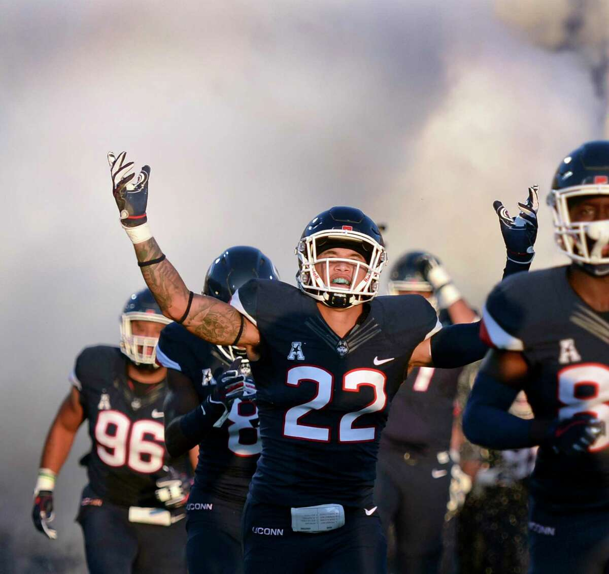 UConn linebacker Eli Thomas (22) raises his arms to the crowd as the Huskies take the field for their opening game of the season against Central Florida on Aug. 30, 2018, in East Hartford.
