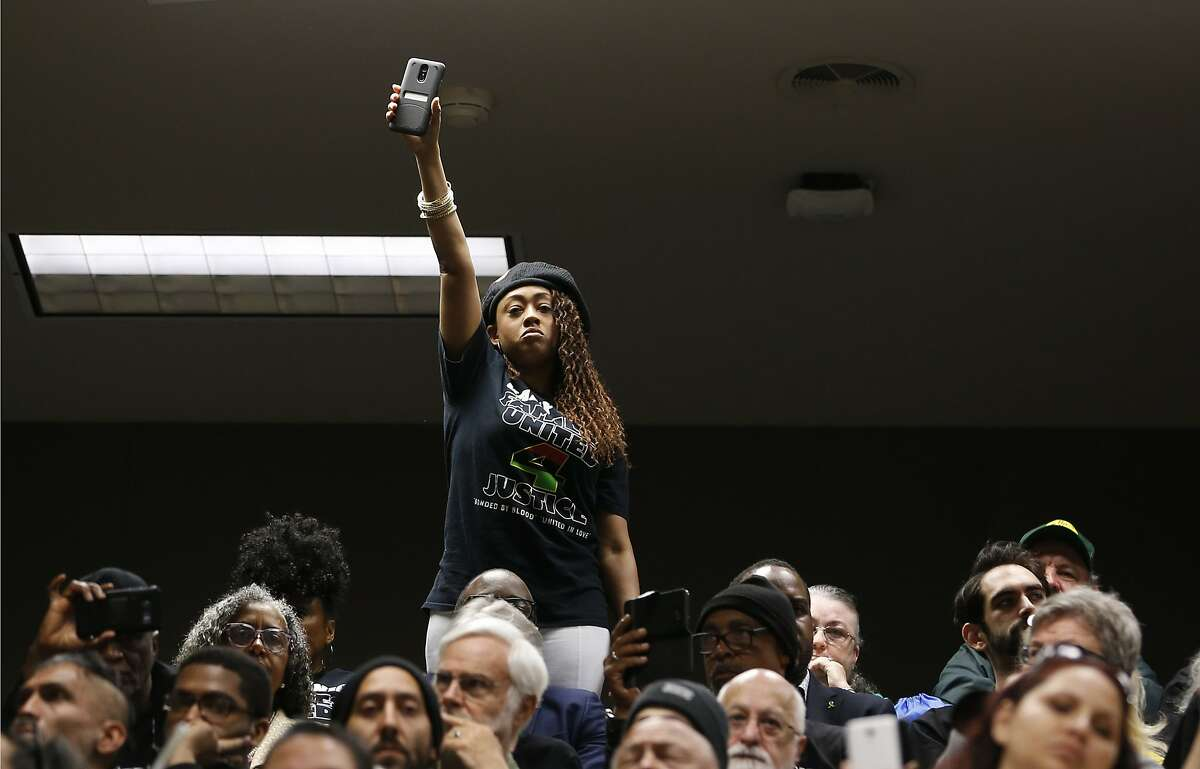 Jamilia Land, a friend of the family of police shooting victim Stephon Clark, holds up a cellphone during a hearing on legislation to restrict the use of deadly force by police, Tuesday, April 9, 2019, in Sacramento, Calif. Sacramento Police officers mistook the cellphone Clark was holding for a gun when he was shot and killed in 2018. (AP Photo/Rich Pedroncelli)