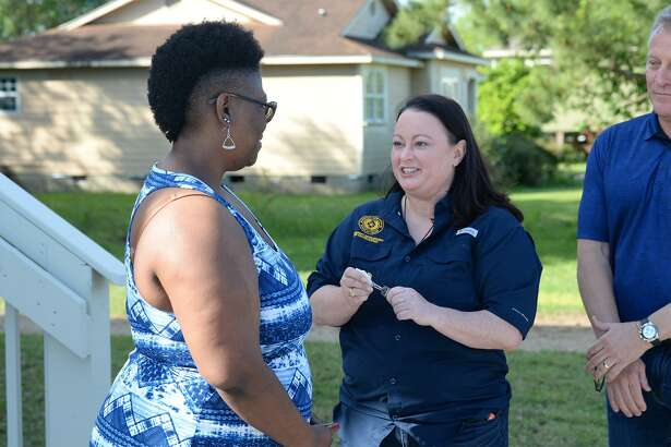 The General Land Office's Brittany Eck hands keys to a brand new home to Havalisia Owens in Port Acres on Friday. Owens' home was ruined by Harvey, then demolished and replaced by the GLO. Photo taken Friday, 4/19/19