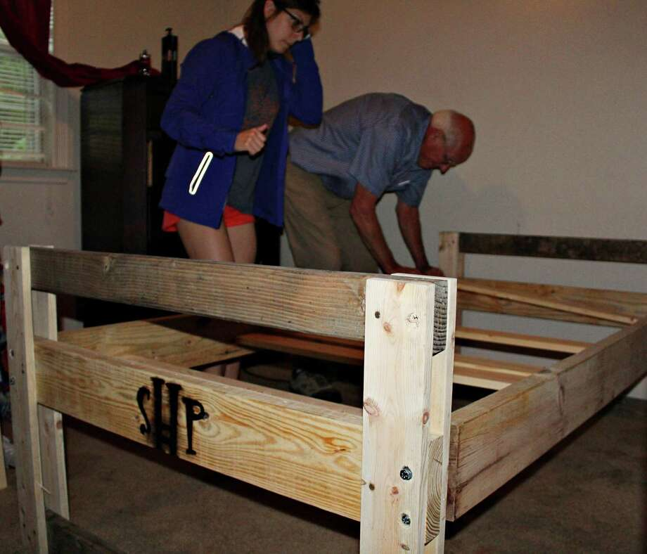 Jack Seeley and Megan Smith assemble the bed in an 11-year-old's bedroom. Photo: Photo By: Erica Apodaca/The Enterprise