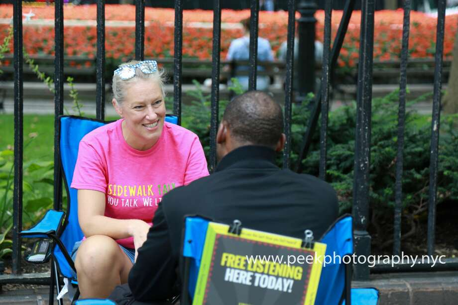Traci Ruble, the founder of Sidewalk Talk, chatting on the sidewalk. Photo: Courtesy: Traci Ruble/Sidewalk Talk