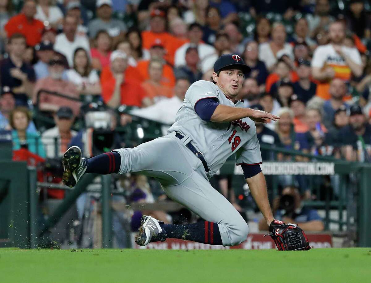 Minnesota Twins relief pitcher Ryne Harper (19) falls backward making the throw to first as Houston Astros Josh Reddick ground out during the sixth inning of an MLB baseball game at Minute Maid Park, Tuesday, April 23, 2019, in Houston.