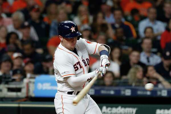 Houston Astros third baseman Alex Bregman (2) hits his RBI single during the fifth inning of an MLB baseball game at Minute Maid Park, Tuesday, April 23, 2019, in Houston.