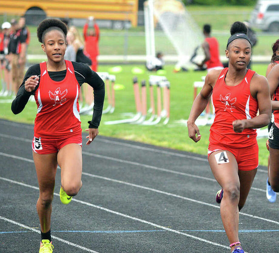 Alton's Renee Raglin (left) and Jeanea Epps head down the stretch in the girls' 100-meter dash at Tuesday's Madison County Large School Track Meet at Triad. Epps finished first in a time of 12.34 seconds and Raglin was second in 12.54. Photo: Scott Marion | For The Telegraph