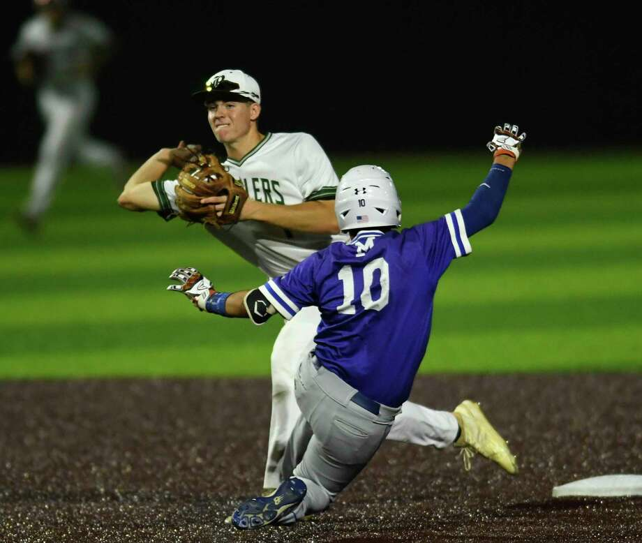 Reagan second baseman Jacob Burcham turns a double play as MacArthur's Jacob Gilbert slides in to end the game during the 27-6A baseball action at the NEISD Sports Park on Tuesday, April 23, 2019. Photo: Billy Calzada, Staff / Staff Photographer / San Antonio Express-News