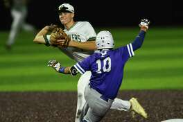 Reagan second baseman Jacob Burcham turns a double play as MacArthur's Jacob Gilbert slides in to end the game during the 27-6A baseball action at the NEISD Sports Park on Tuesday, April 23, 2019.
