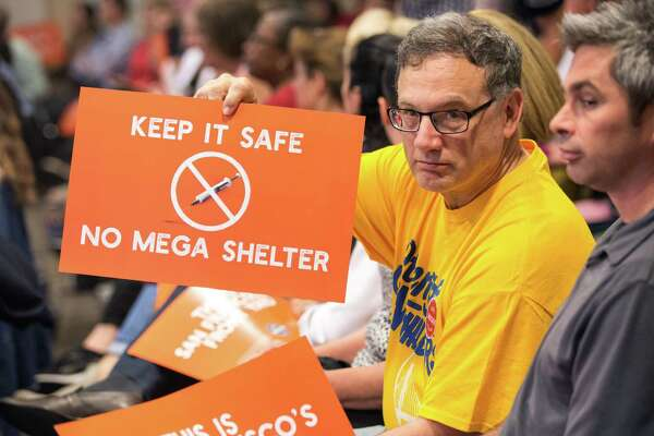 Bruce Guldetsky holds a sign expressing many neighbors' feelings, during the packed, 5½-hour Port Commission meeting.