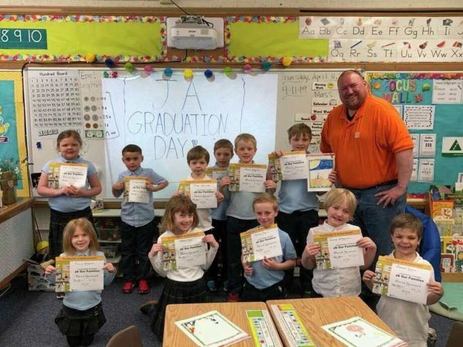 The first-grade class of Tricia Maxheimer at Blessed Sacrement School in Midland recently from graduated the Junior Acheivement Business School. The five-week program lead by JA volunteer Alan Osburn from Home Depot taught students how businesses help our neighborhoods, the importance of education and how to start a business. All 12 students made a final presentation on what they would like their job to be when they grow up, with four of them planning on playing baseball for the Great Lakes Loons. Teachers interested in hosting the volunteer-based program in their classroom are encouraged to contact the Midland Junior Acheivement Office. (photo provided)