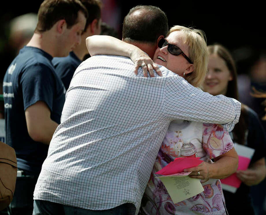 Attendees hug Saturday before a program for victims of the massacre at Columbine High School 20 years ago in Littleton, Colorado. Photo: David Zalubowski | Associated Press