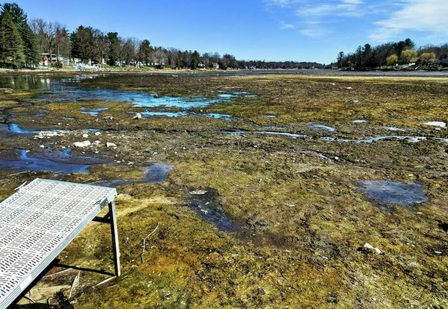 Small puddles of water cover Wixom Lake Saturday, as seen from the Wixom Lake Gas and Launch. Four Lakes Task Force board members are hoping to see a rise by Memorial Day. The lake is down eight feet. (Teresa Nims/for the Daily News)