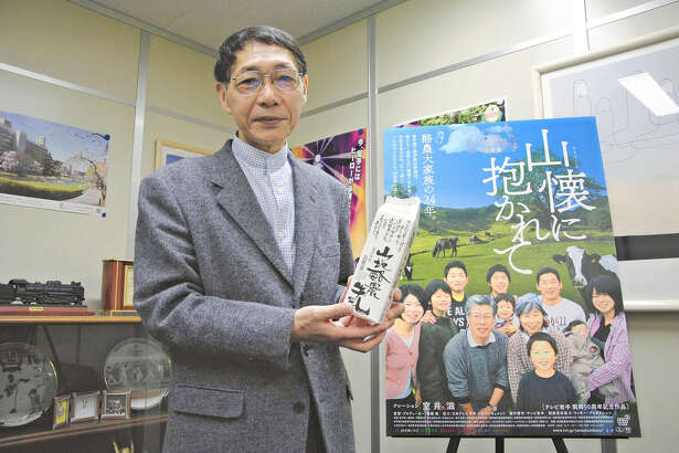 "Takashi Endo, director of the documentary film ""Yamafutokoro ni Idakarete,"" displays a carton for Yoshizuka's milk."