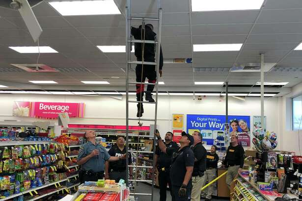 Four suspects are in custody after police found them barricaded within the ceiling of a CVS Wednesday. One of the suspects hid in an exterior concrete column outside of the store, police said.