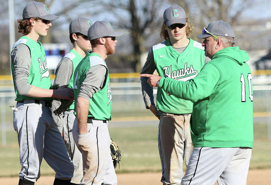 Carrollton coach Jeff Krumwiede (right), shown meeting with Hawks infielders during a March 22 win at Roxana, and his Hawks were in Hardin on Tuesday and stayed unbeaten in the WIVC South with a victory over Calhoun. Photo: Greg Shashack / The Telegraph