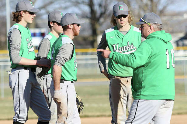 Carrollton coach Jeff Krumwiede (right), shown meeting with Hawks infielders during a March 22 win at Roxana, and his Hawks were in Hardin on Tuesday and stayed unbeaten in the WIVC South with a victory over Calhoun.