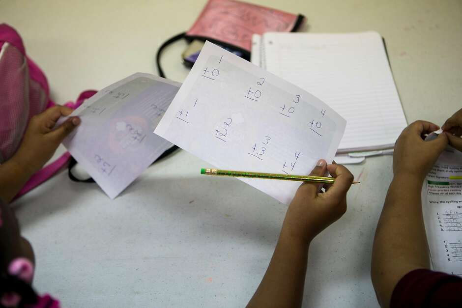 A participant in an after-school program holds up arithmetic flashcards during the after-school program.