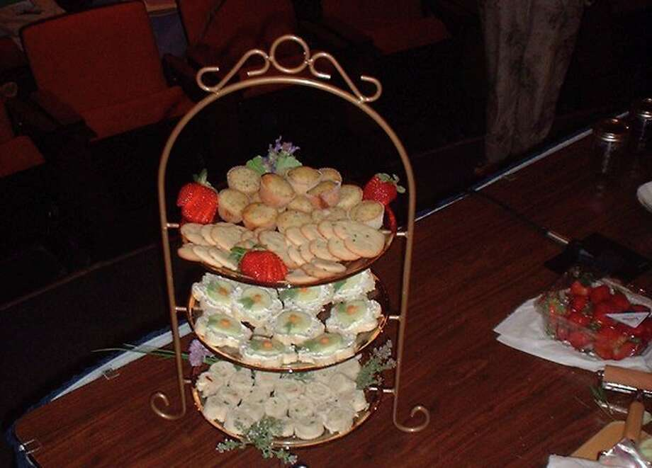 Cucumber sandwiches featuring herbed cheese are shown on the middle tier of a display rack.