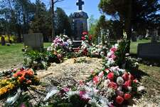 The gravesite of famed ghost hunter and Monroe resident Lorraine Warren is festooned with flowers following her burial at Stepney Cemetary in Monroe, Conn. on Wednesday, April 24, 2019.