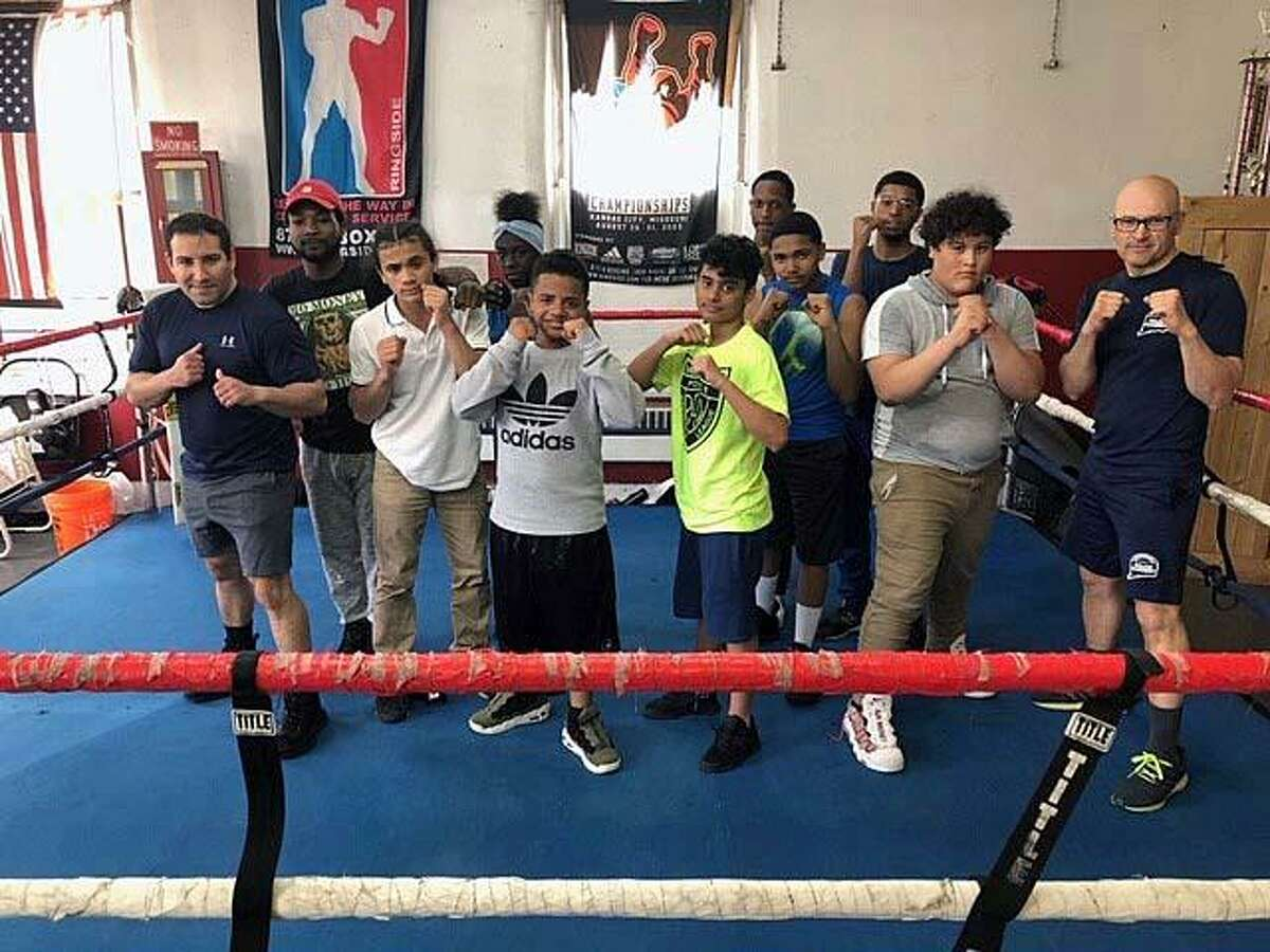 Bridgeport Police School Resource Officer Eroildo Quiles (right) with students from the Bridgeport, Conn., youth boxing program, launched on Tuesday, April 23, 2019.