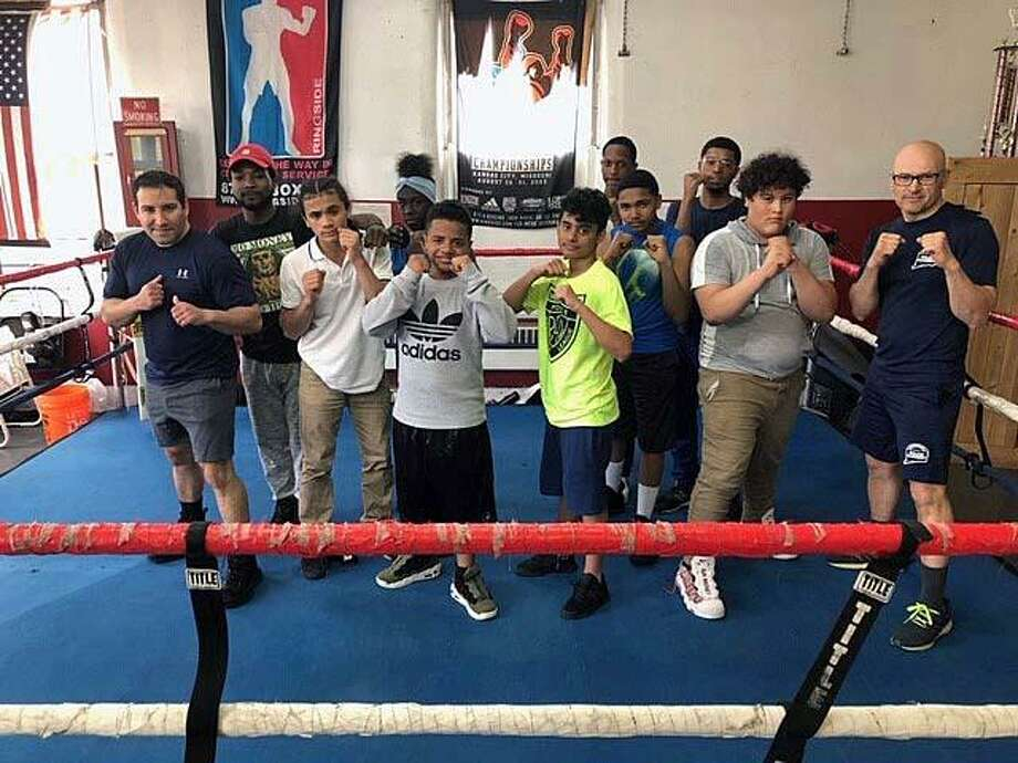 Bridgeport Police School Resource Officer Eroildo Quiles (right) with students from the Bridgeport, Conn., youth boxing program, launched on Tuesday, April 23, 2019. Photo: Contributed Photo / Bridgeport Police Department / Contributed Photo / Connecticut Post Contributed