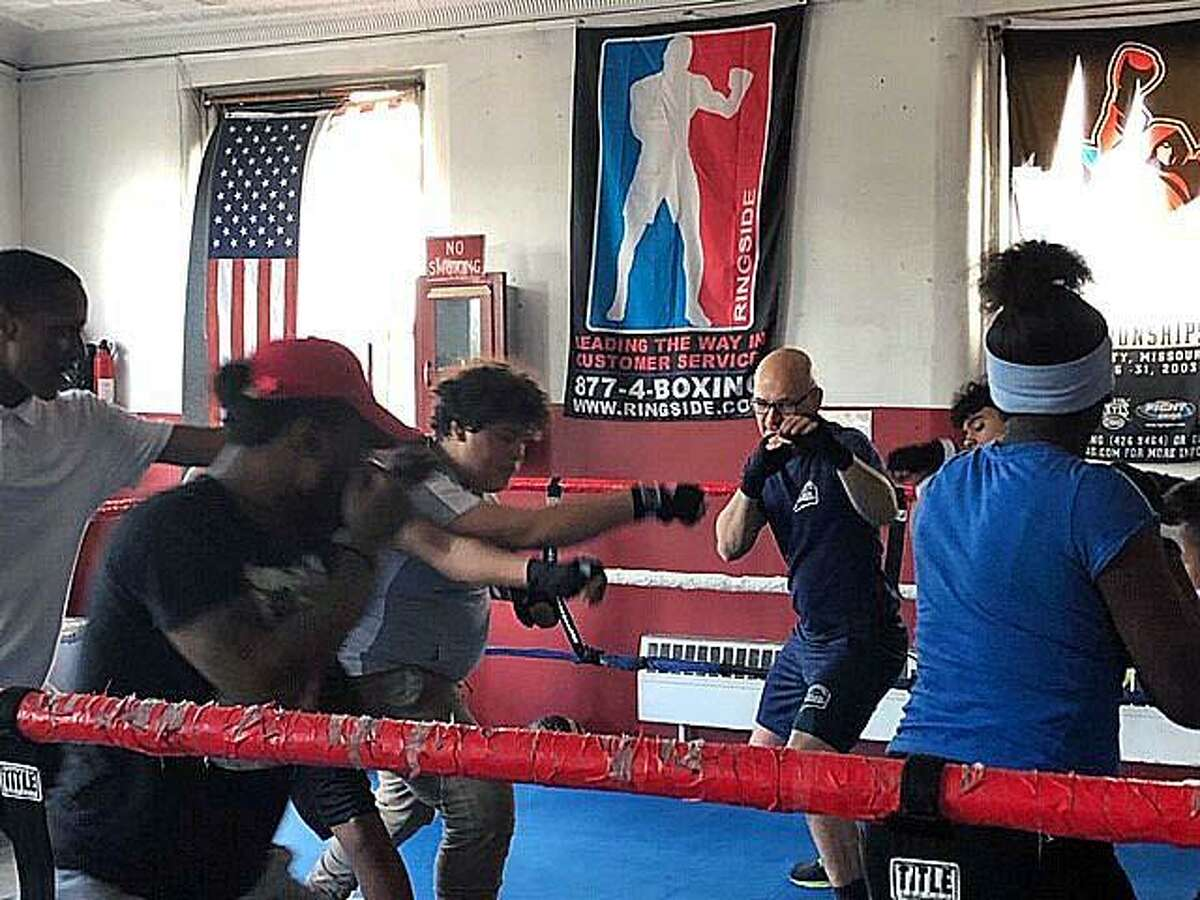 Bridgeport Police School Resource Officer Eroildo Quiles with students from the Bridgeport, Conn., youth boxing program, launched on Tuesday, April 23, 2019.