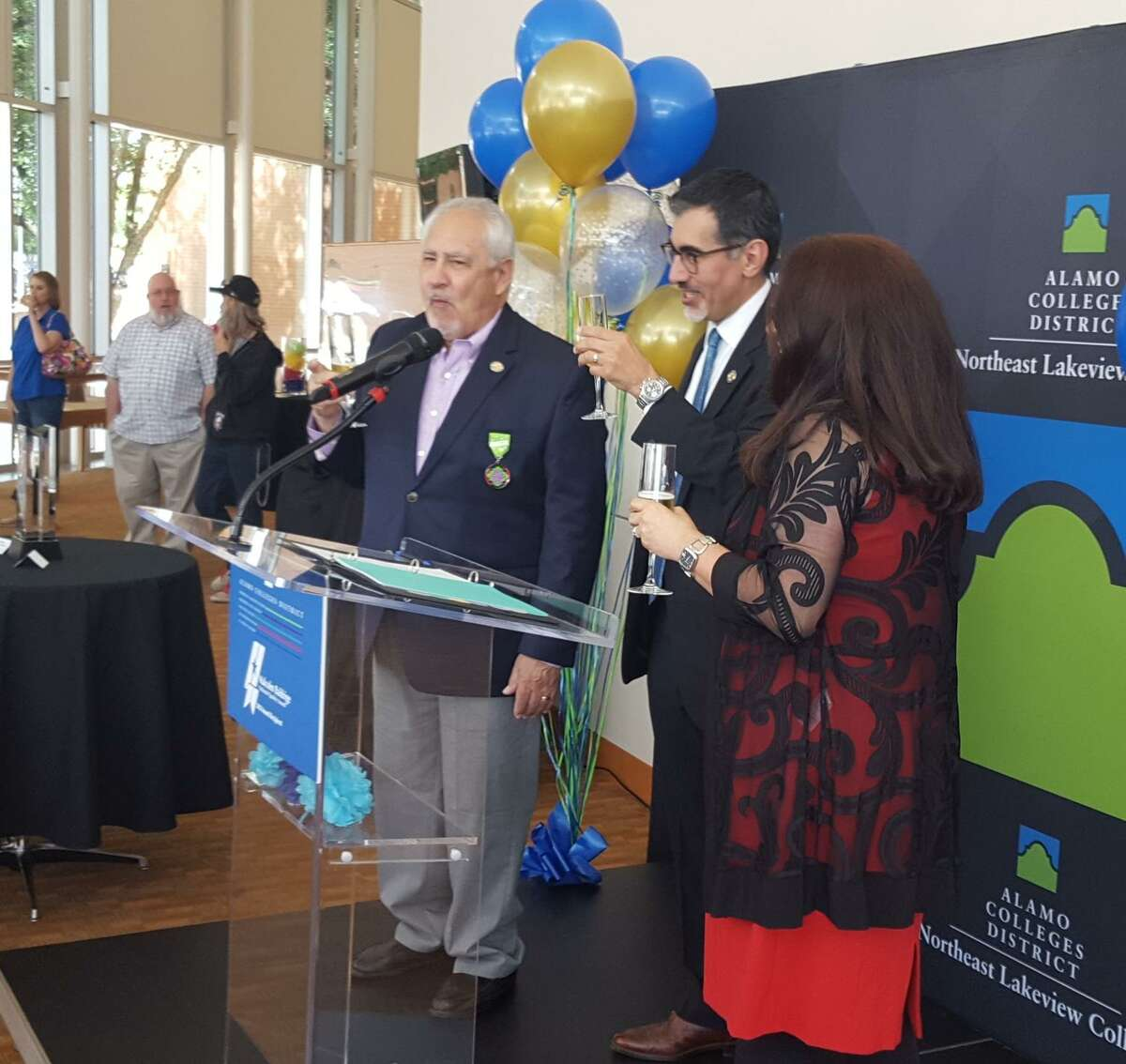 Mike Flores, Alamo Colleges District chancellor (center) raises his glass in a toast during an April 18 event at Northeast Lakeview College, celebrating the district's receipt of the Malcolm Baldrige National Quality Award. With Flores are ACD District Trustee Joe Jesse Sanchez, left, and Northeast Lakeview College President Veronica Garcia.