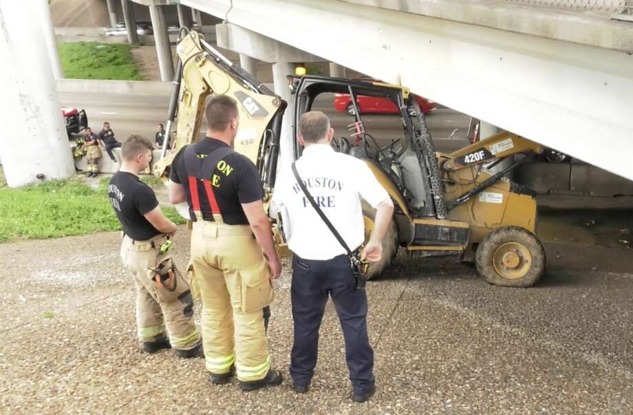 Houston firefighters and construction crews work to dislodge a piece of equipment accidentally driven into the Alabama Street bridge over the Southwest Freeway on Wednesday, April 24, 2019. Photo: Jay R. Jordan
