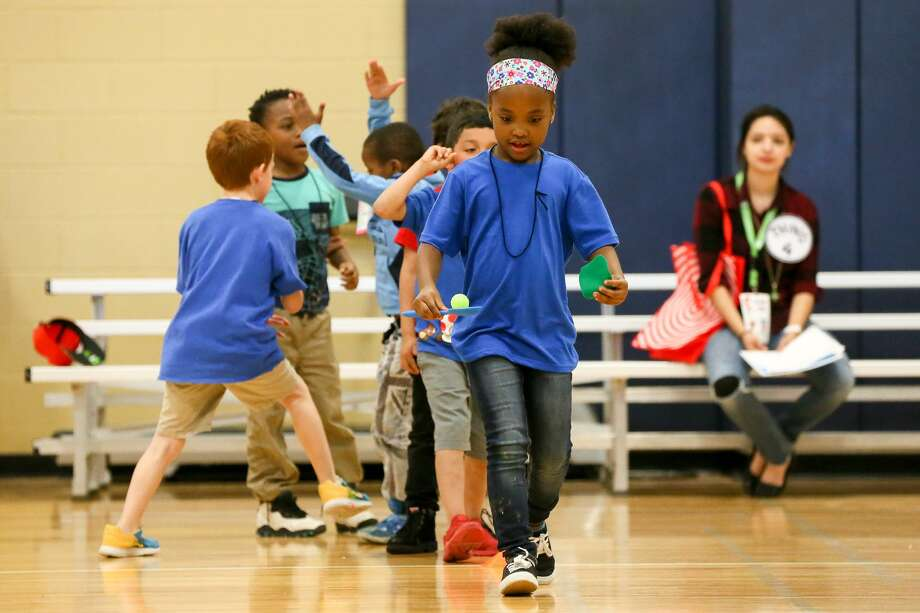 "La'Zaeyah Stewart, a first grader at Candlewood Elementary, balances a green egg and slice of green ham in a relay race during an Adopt-A-School ""Green Eggs and Ham"" day at Northeast Lakeview College on April 16. First graders from Candlewood and Woodstone elementary schools participated in various activities throughout the day, including getting a photograph in a cap and gown and an Egg Hunt. The Adopt-A-School initiative uses structured programming to get students informed and engaged about college and aims to make them more successful as they transition to college-level classwork. Photo: Marvin Pfeiffer /Staff Photographer / Express-News 2019"