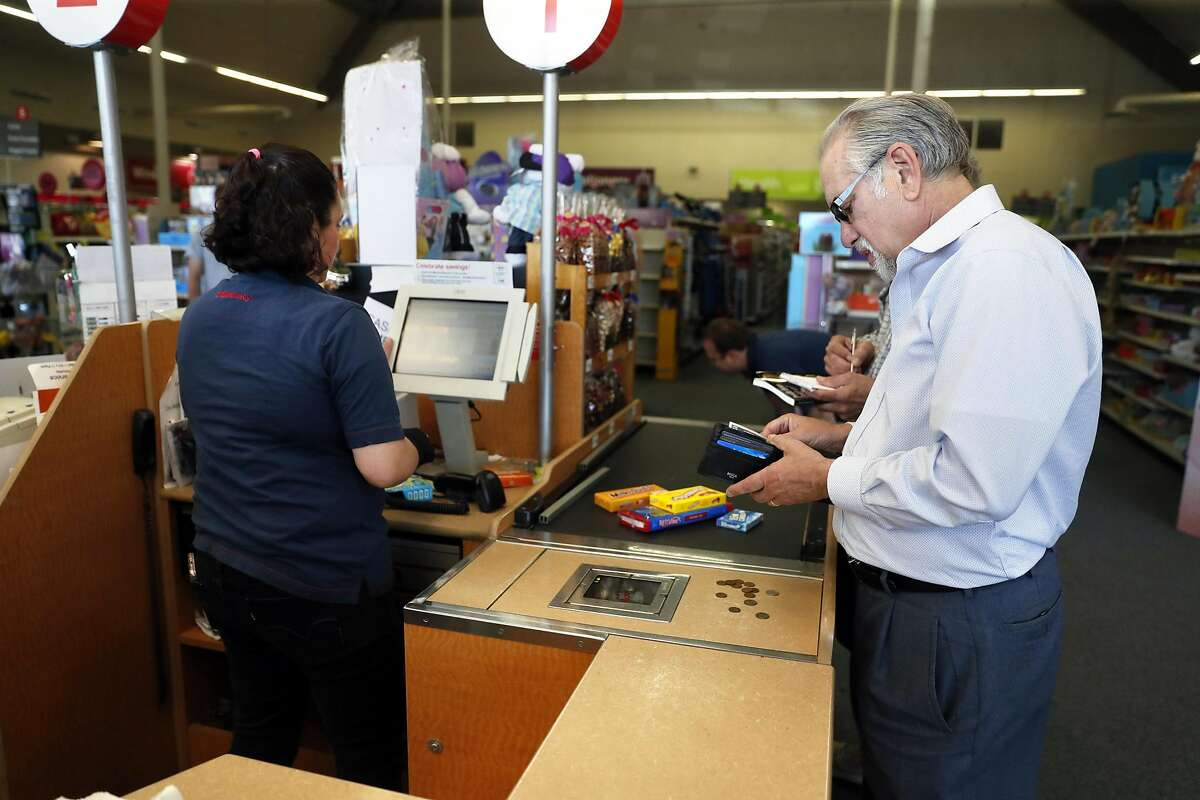 Don Kagin gets ready to pay with rare coins while shopping at a drugstore while taking part in the Great American Coin Hunt in Tiburon, Calif., on Monday, April 22, 2019.
