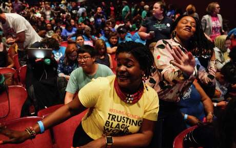 Jasmen Rogers-Shaw, left, and Kelli Ann Thomas, right, both of Miami dance during intermission at the presidential candidate forum sponsored by She the People at Texas Southern University Wednesday, April 25, 2019.