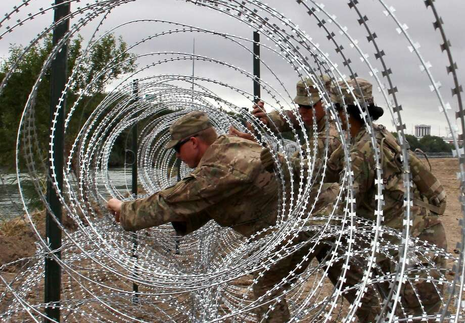 "(FILES) In this file photo taken on November 18, 2018, Soldiers from the Kentucky-based 19th Engineer Battalion install barbed wire fences on the banks of the Rio Grande in Laredo, Texas. - US President Donald Trump said on April 24, 2019, the US is sending armed soldiers to the southern border after Mexican soldiers ""pulled guns"" on US troops. ""Mexico's Soldiers recently pulled guns on our National Guard Soldiers, probably as a diversionary tactic for drug smugglers on the Border. Better not happen again! We are now sending ARMED SOLDIERS to the Border. Mexico is not doing nearly enough in apprehending & returning!"" Trump said on Twitter. (Photo by Thomas WATKINS / AFP)THOMAS WATKINS/AFP/Getty Images Photo: Thomas Watkins, AFP/Getty Images"